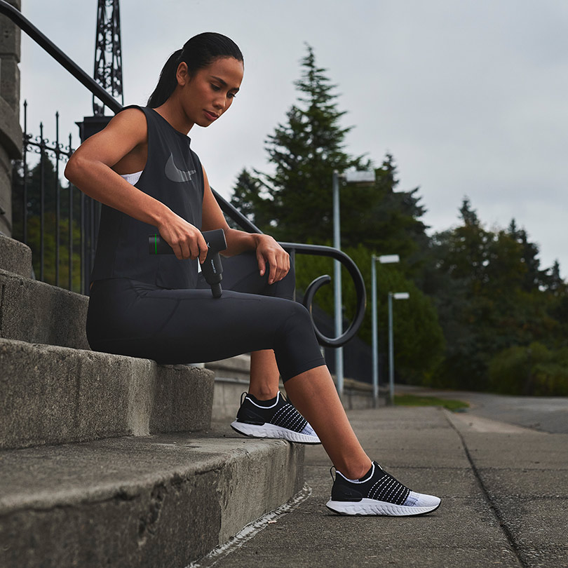 Hypervolt Go being used by female on steps after jog.