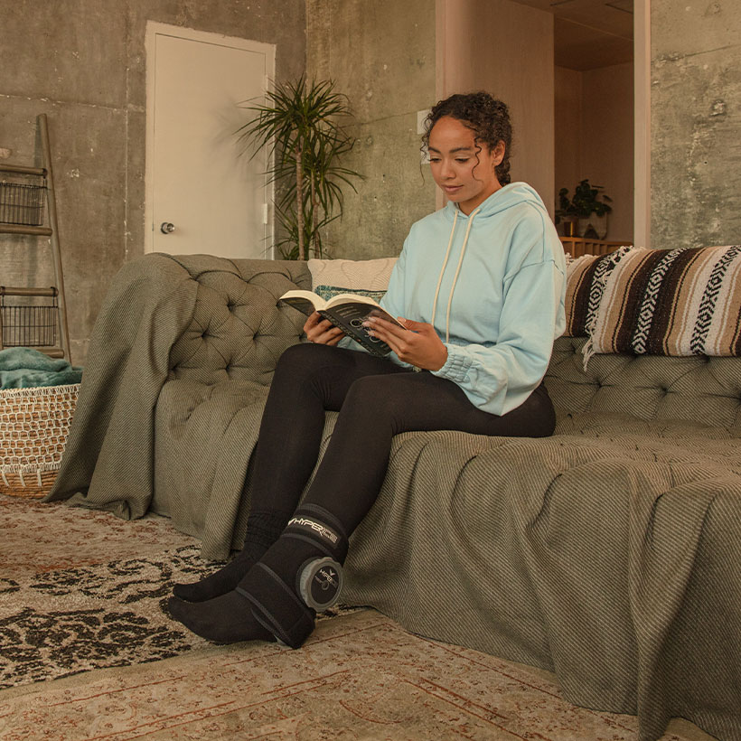 Woman reading with Hyperice Utility wrap on her ankle